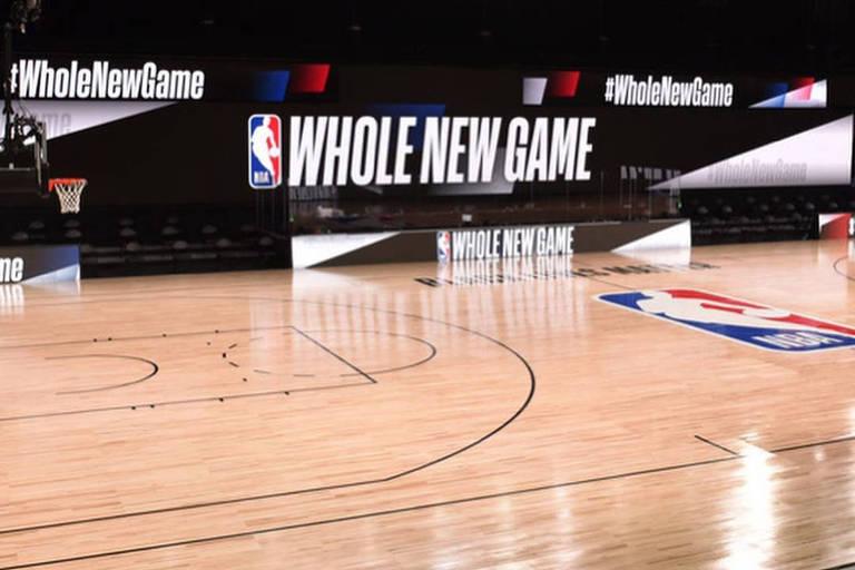 Quadra com logo da NBA ao centro e telões ao fundo