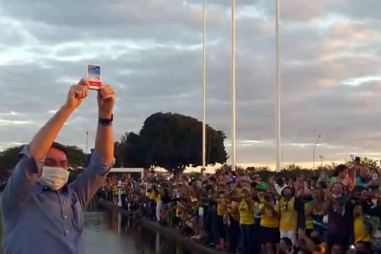 Bolsonaro erguendo uma caixa de remédio. Ao fundo dele, pessoas com camisetas amarelas