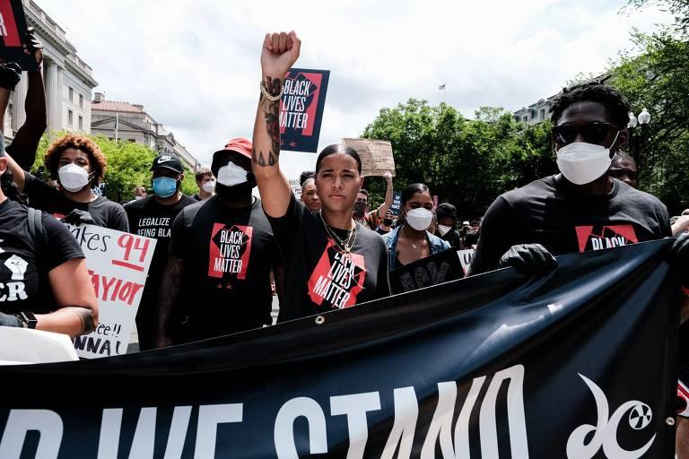 Natasha Cloud com o braço erguido, ao lado de outros manifestantes e atrás de uma faixa