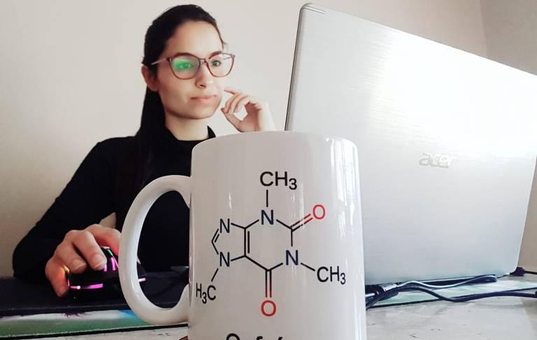 Mulher com óculos e cabelo preso usa notebook em mesa, há uma caneca com desenho de molécula em primeiro plano