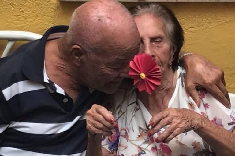 idoso de camisa branca e preta abraçado a idosa com rosa de plástico na mão