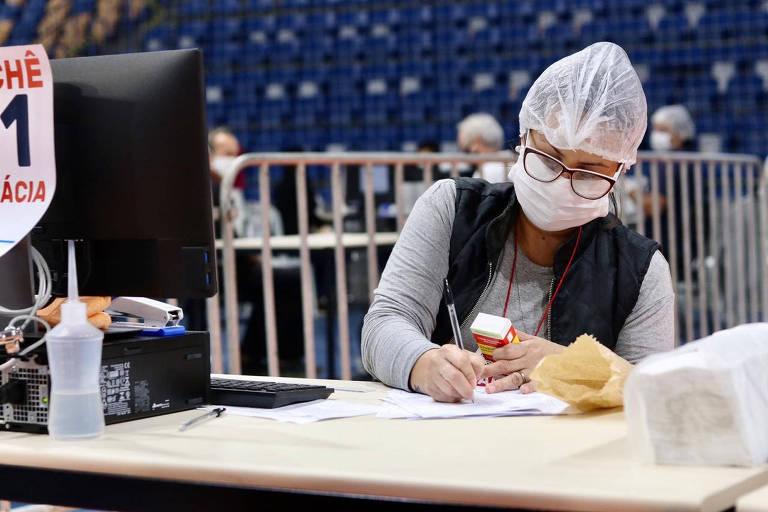 Mulher, usando máscara e touca, segura caixa de remédio e faz anotação em centro de distribuição de ivermectina