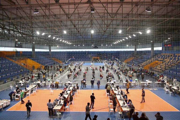 Quadra de esportes com diversas cadeiras e mesas espalhadas, em que há triagem de público