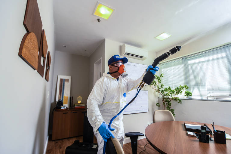 Homem protegido com macacão, máscara, óculos e luvas limpa escritório com uma mangueira de onde sai um vapor