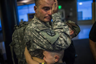 After a two week leave from his deployment to Afghanistan, Sgt. 1st Class Brian Eisch says goodbye to his sons Joey and Isaac before boarding his flight in Appleton, Wis., on Sept. 18, 2010. (Marcus Yam/The New York Times)