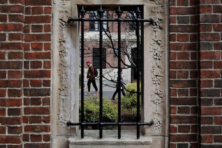 Estudantes caminham em jardim da Universidade Harvard, em Cambridge, no estado de Massachusetts