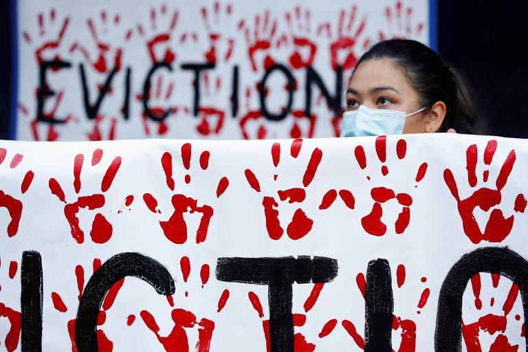 Ativista protesta em San Diego, na Califórnia, com cartaz que diz 'despejos = morte'