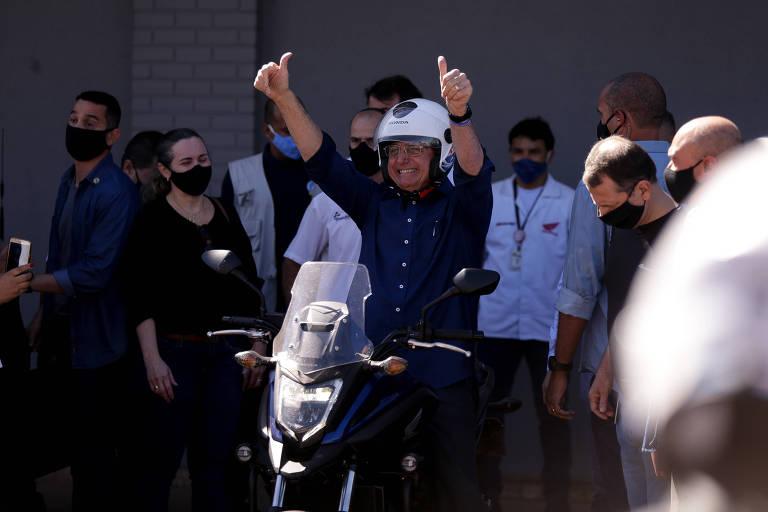 bolsonaro está sentado em garupa de uma moto, com os braços pra cima, e não usa máscara de prevenção