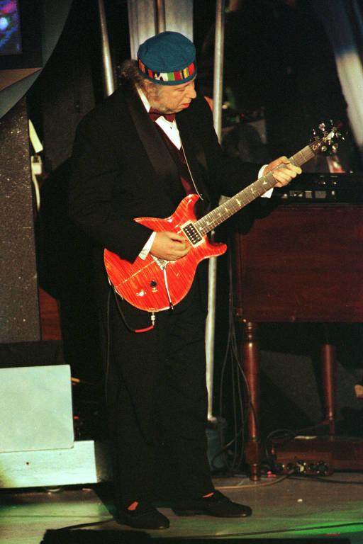 homem de terno preto tocando guitarra vermelha co bandana na cabeça