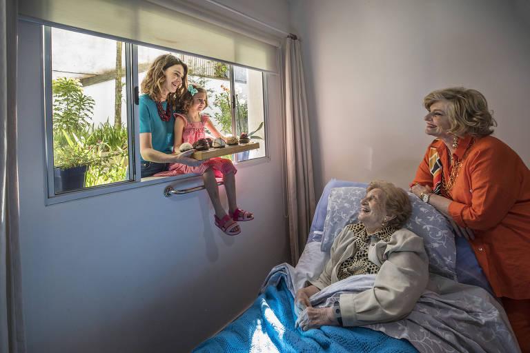 mulher idosa deitada na cama; sua neta e bisneta estão na janela do quarto e sua filha está na cama ao seu lado