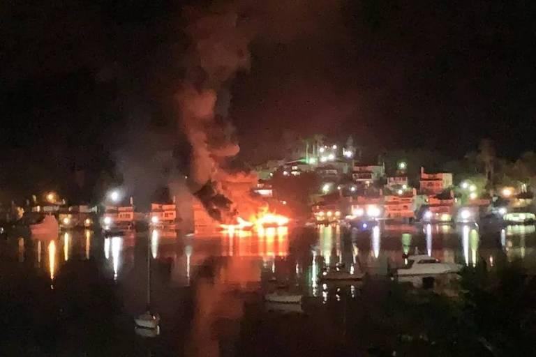 Dois barcos pegando fogo em condomínio de Angra dos Reis, à noite