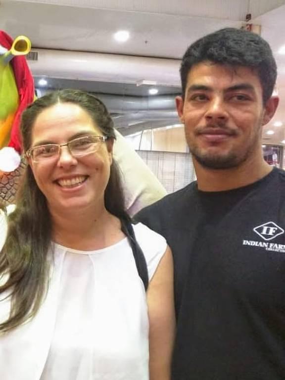Na imagem, há um casal: uma mulher de óculos e camisa branca e um homem ao lado dela de camiseta preta.