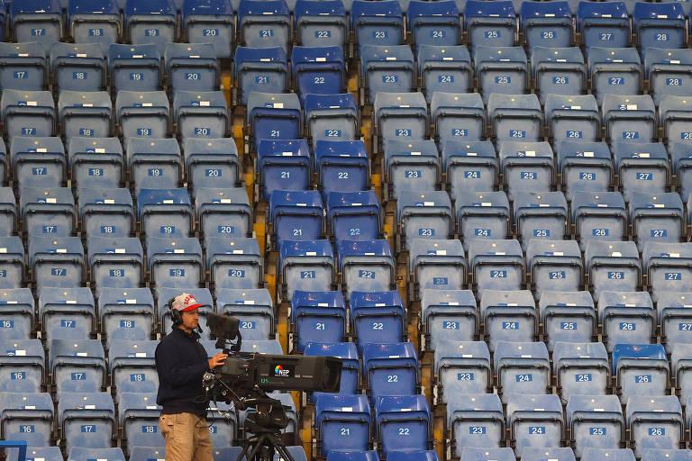 Operador de câmera em jogo entre Chelsea e Norwich pela Premier League, com portões fechados