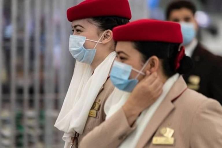 Duas mulheres com uniforme de comissárias de bordo e máscaras