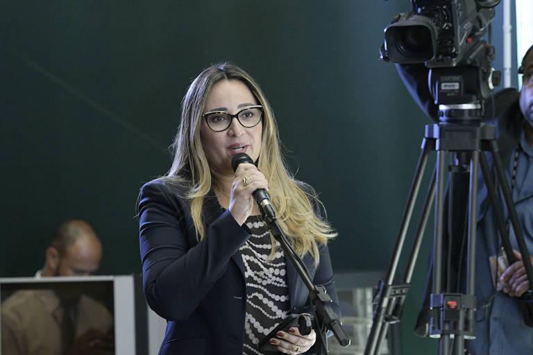 Rejane falando ao microfone perto de um tripé com uma câmera de vídeo