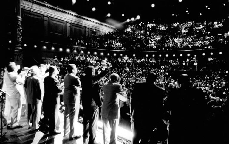 Um grupo de homens, enfileirado, está em cima de um palco cumprimentando a plateia de um teatro