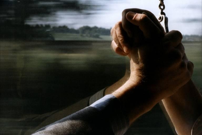 Uma mão segura outra, que está acorrentada, à frente de uma paisagem em movimento