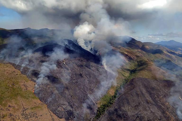 A fumaça de um incêndio se espalha pelo céu. Vegetação de uma montanha queima.