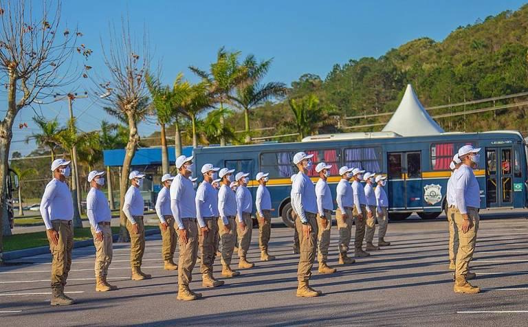 Futuros agentes da PRF aparecem enfileirados em formação militar. Usam máscaras e estão vestidos uniformemente.