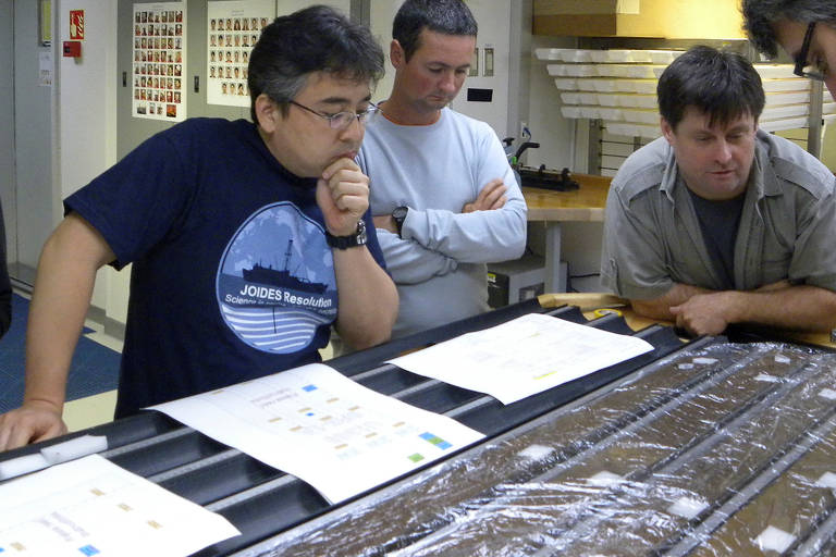 Da esq. para a dir., Yuki Morono, Laurent Toffin e Steven D'Hondt trabalhando no material coletado sob o solo do oceano Pacífico; na foto os pesquisadores estão debruçados sobre uma mesa com papéis e outros materiais