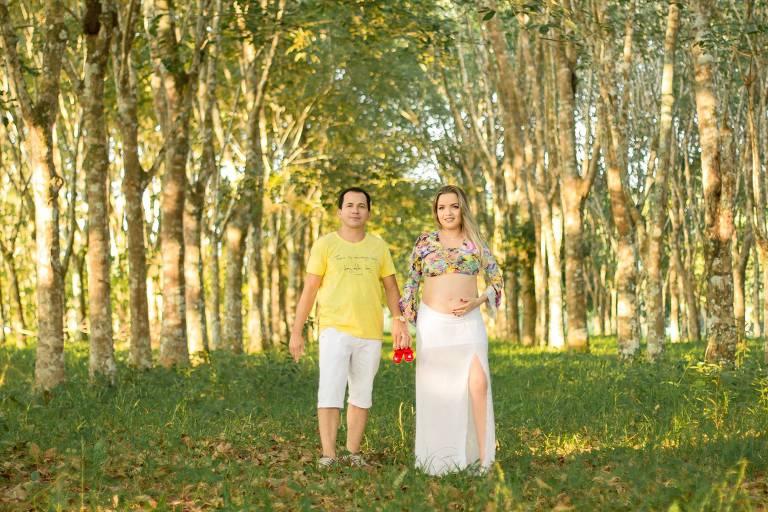 Raimundo Castro e esposa Patydan Castro, vítima de coronavírus; o casal se encontra num campo, entre árvores, e ela mostra a barriga de grávida entre uma blusa curta e uma saia longa