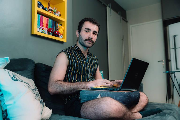 Jovem sentado no sofá usando computador