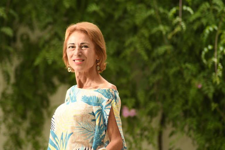 Mulher com blusa de estampa com folhas sorri para foto; atrás dela há uma folhagens