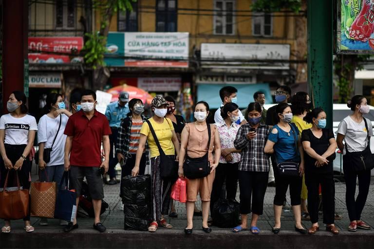 Pessoas esperam em ponto de ônibus em Hanói