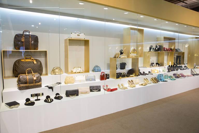 Bolsas e sapatos de Hebe Camargo expostos atrás de um vidro