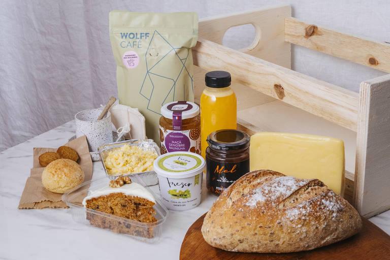 Caixote de café da manhã da Estela Passoni inclui, além de xícara e coador, itens como café; pão de fermentação natural; broa; bolo de cenoura; pão de queijo; geleia; mel; suco de laranja