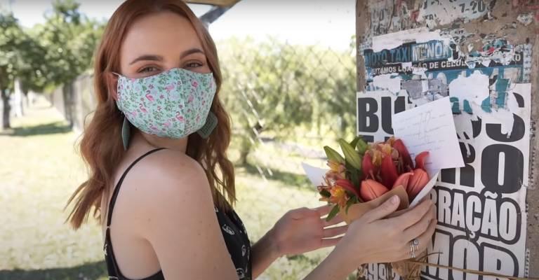mulher de máscara segura flores em arranjo encostado em pilar de ponto de ônibus