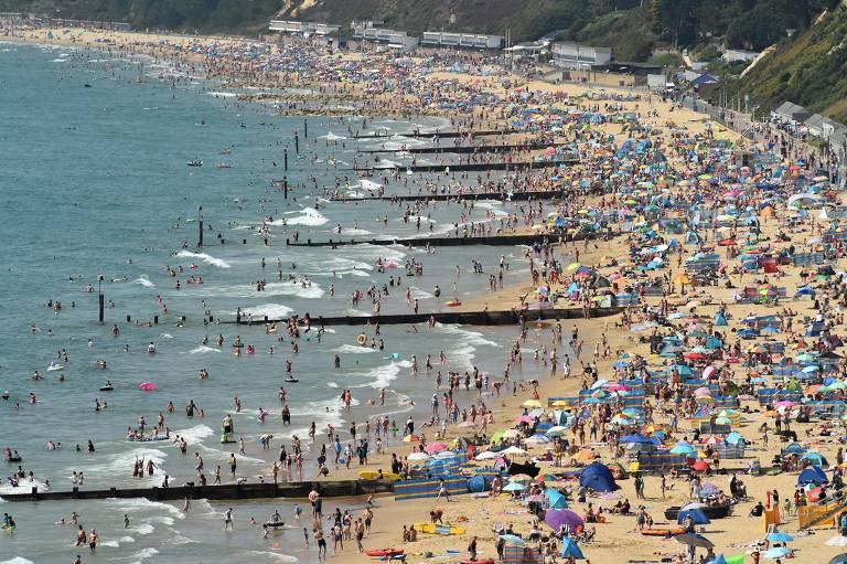 Imagem aberta mostra dia ensolarado e faixa de areia lotada por banhistas; muitos também estão dentro da água