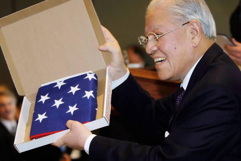 Lee segura bandeira americana que recebeu como presente do congressista dos EUA Brad Sherman durante visita a Los Angeles, em 2005