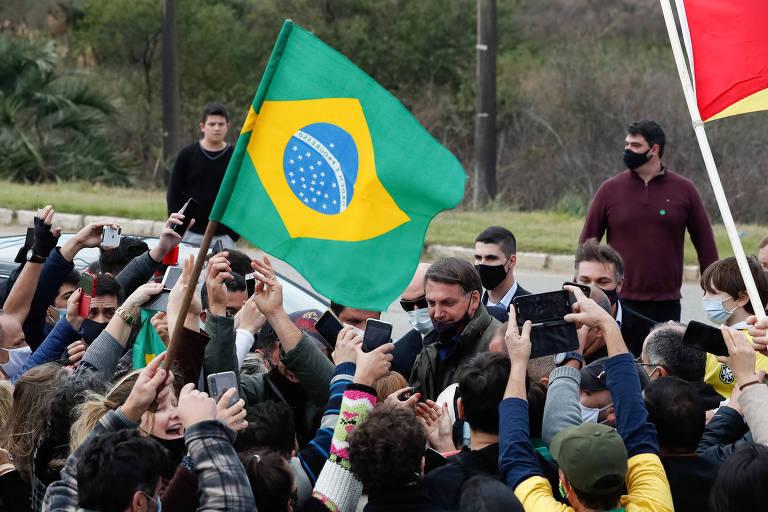 Bolsonaro cercado por por apoiadores, que apontam celulares e estendem as mãos. Um  deles estente uma bandeira do Brasil. O presidente usa máscar preta, mas o nariz e parte da boca estão descobertos