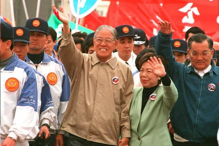 Li Teng-hui (esq.), sua esposa, Tseng Wen-hui (centro), e o vice de sua chapa, Lian Chan (dir.), acenam para o público em um ginásio esportivo durante campanha eleitoral de 1996