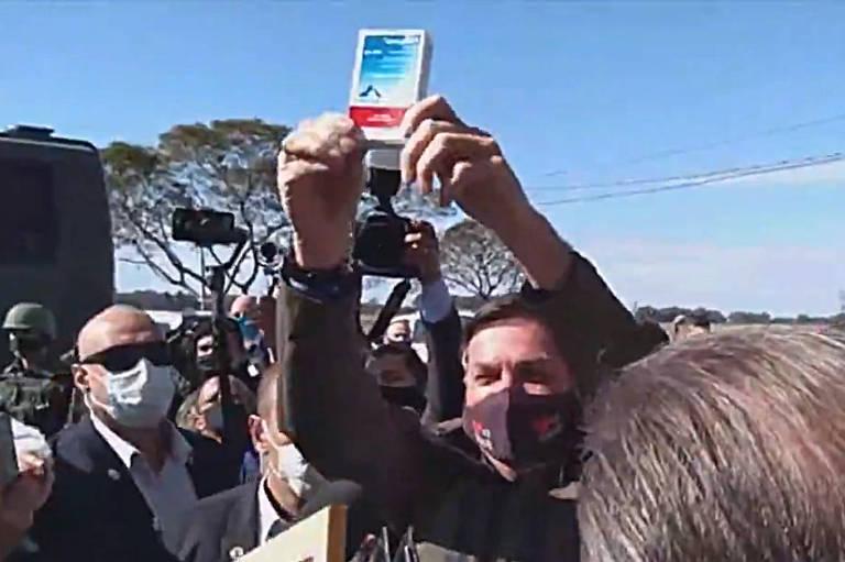 Jair Bolsonaro cercado de pessoas e erguento erguendo uma caixa de remédio