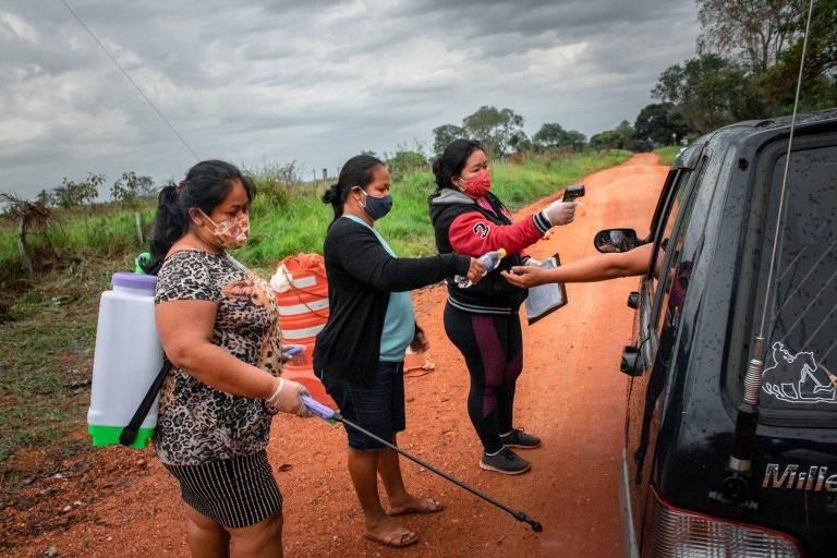 Mulheres seguram termômetro e equipamento para desinfecção de pneus de veículos