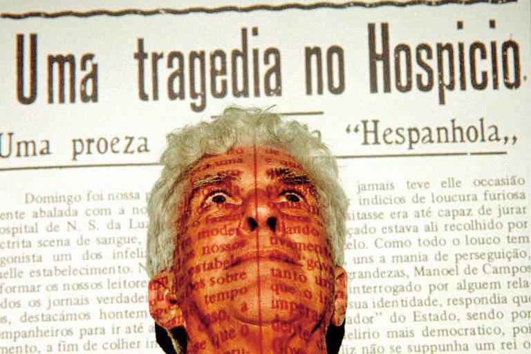"""O escritor Valêncio Xavier à frente de reprodução em slide de uma das páginas de seu livro """"O Mez da Grippe"""", em 1998"""