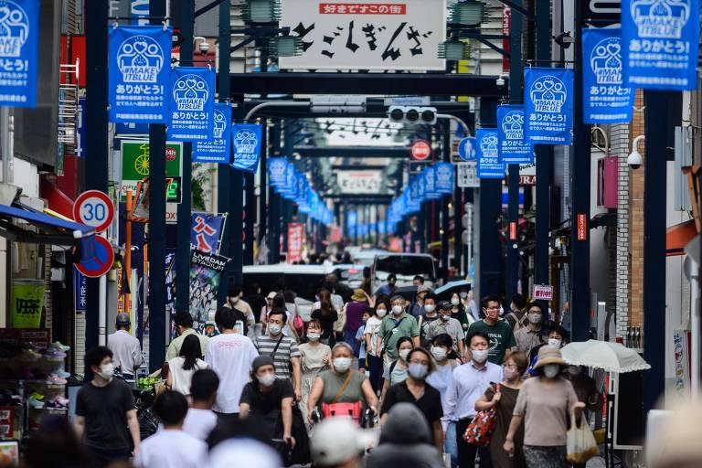 Rua vista em perspectiva com pessoas de máscaras e faixas azuis no alto da foto