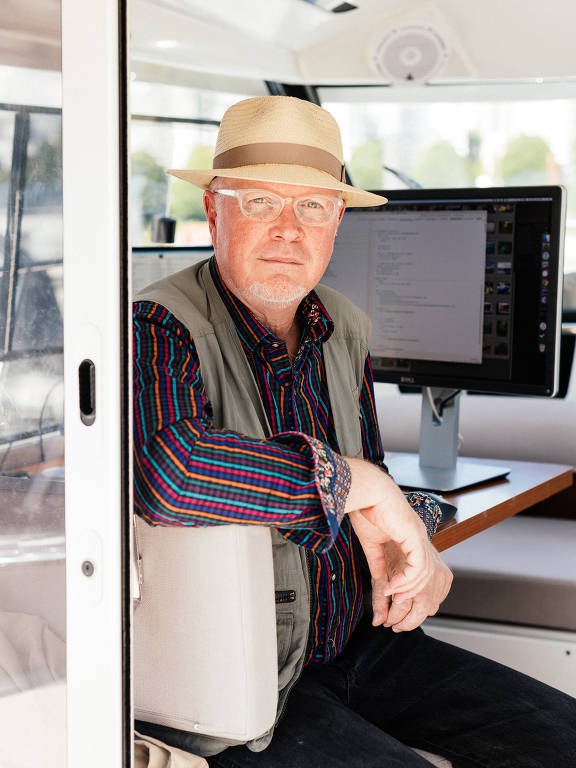 Tim Brady é um senhor de idade que usa chapéu de palha, colete verde e camisa social colorida listrada. Ele está sentado com o braço apoiado na cadeira