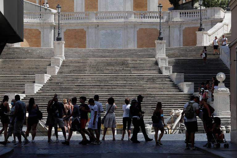 Pedestres passam pela Piazza di Spagna, em Roma, após relaxamento das medidas de combate ao novo coronavírus