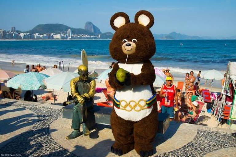 O urso Misha, mascote dos Jogos Olímpicos de 1980, posa com a estátua de Carlos Drummond de Andrade, no Rio de Janeiro, em 2014