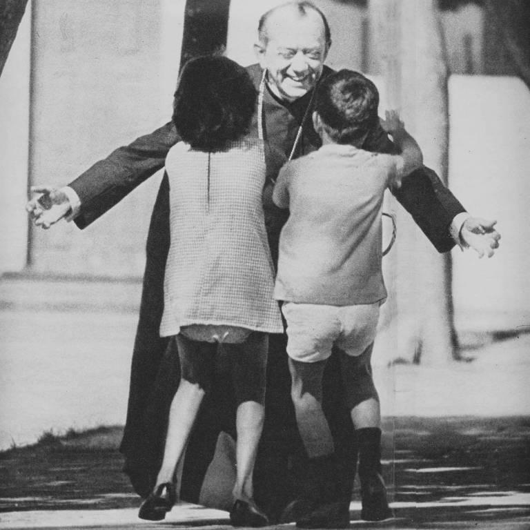 Dom Hélder Câmara abraçando duas crianças