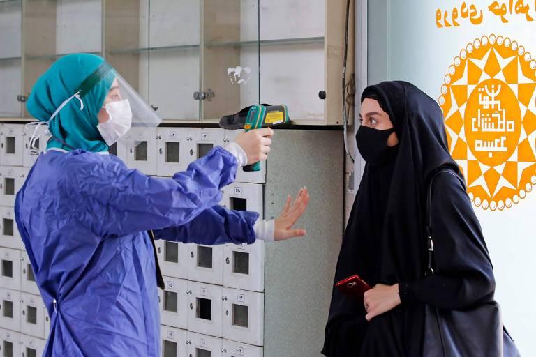 Profissional de saúde checa temperatura de mulher iraniana no campus da Universidade de Teerã