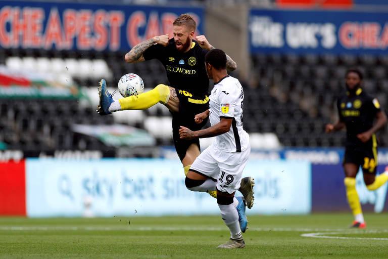 Pontus Jansson, do Brentford (à esq.) disputa bola durante a semifinal dos playoffs da segunda divisão