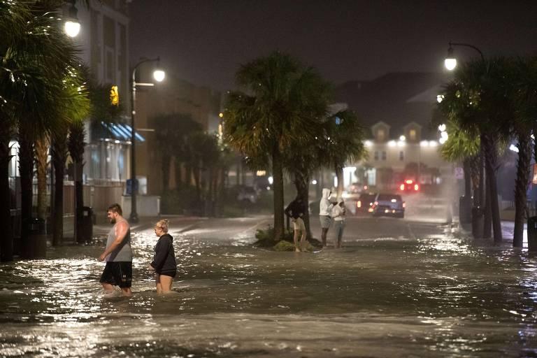 Duas pessoas caminham em rua alagada com água até os joelhos