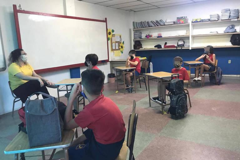 Crianças sentadas em cinco carteiras espaçadas com professora de máscara à frente