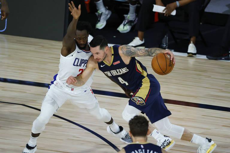 JJ Redick, do New Orleans Pelicans, conduz a bola marcado por adversário em partida contra o Los Angeles Clippers na volta da NBA