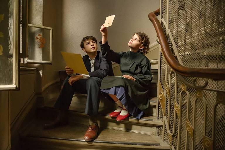 Duas crianças estão sentadas numa escadaria. Do lado esquerdo está o menino, mais velho, segurando um papel. Do lado direito, a menina observa um envelope contra a luz do sol