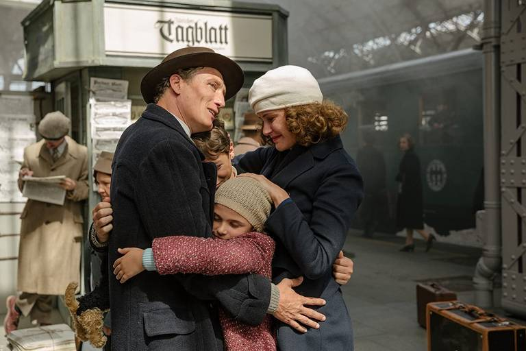 Uma família se abraça numa plataforma de uma estação de trem. Eles usam roupas do início do século XX e sorriem